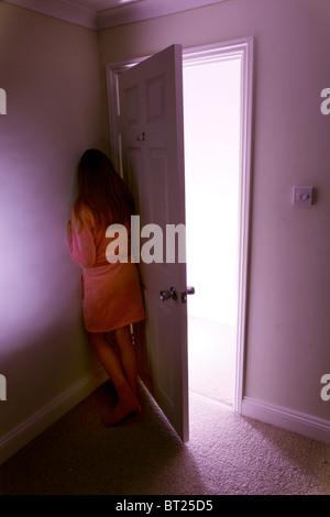 Girl in dressing gown hiding behind an open bedroom door - Stock Photo