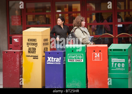 A woman stands by newspapers boxes in Ottawa Sunday September 26, 2010. - Stock Photo