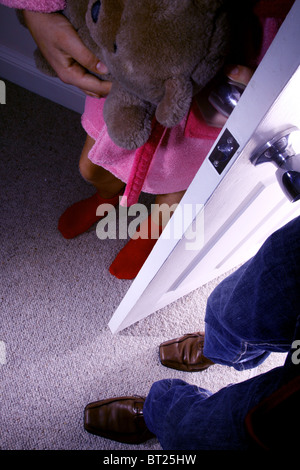 Male feet entering a young girls bedroom while she clutches a teddy bear. No faces shown - Stock Photo