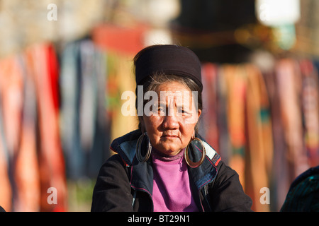 Black Hmong woman waiting for tourist to sell one of her blankets to a the market in Sapa, Vietnam - Stock Photo