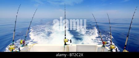 boat fishing trolling panoramic rod and reels blue sea wake - Stock Photo