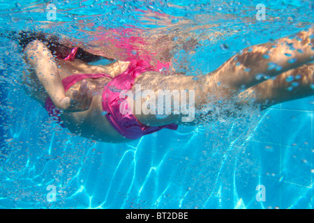 underwater pink bikini little girl swimming in blue pool - Stock Photo
