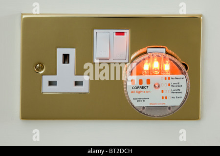 UK 3 pin electric wall socket tester plug checking mains electricity power supply wiring with three indicator lights on to show correct connections