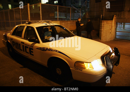 Police officer stops a man in an alley late at night, Vancouver, British Columbia, Canada - Stock Photo