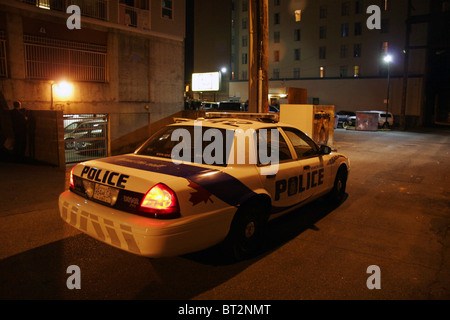 Police car in an alley late at night, Vancouver, British Columbia, Canada - Stock Photo