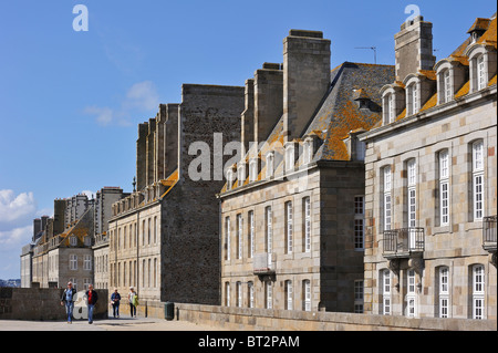 Tourists walking on the town ramparts and typical houses at Saint-Malo, Brittany, France - Stock Photo