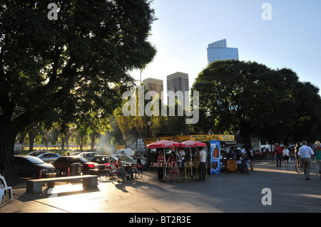 People eating and putting sauce on fast-food in front of a mobile parilla grill, Costanera Sur Boulevard, Buenos - Stock Photo