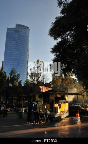 Two men, standing at a table by the side of a parilla grill, putting sauce on fast-food, Costanera Sur Boulevard, - Stock Photo