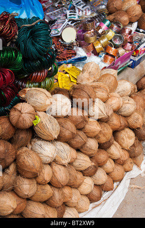 Coconuts and womans jewelry for sale at an Indian street market. Puttaparthi, Andhra Pradesh, India - Stock Photo
