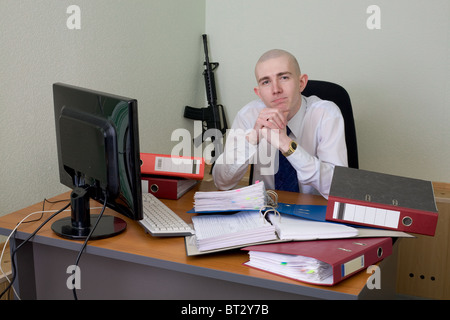 The chief in a white shirt on a workplace with a rifle on a background - Stock Photo