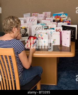 A woman looks depressed while looking at her 21st birthday 'key' while surrounded by cards celebrating her 60th - Stock Photo