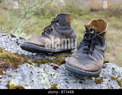 Standing on a stone, the old torn boots - Stock Photo