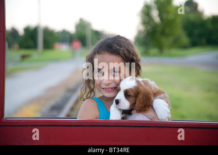 Girl holding a Cavalier King Charles Spaniel puppy dog - Stock Photo