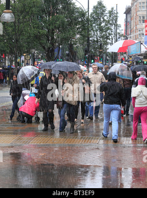 Oxford Street Shoppers on a cold and rainy day. - Stock Photo