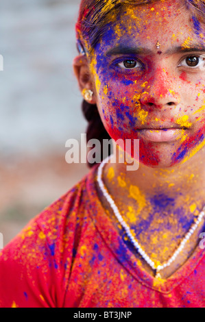 Young Indian girl covered in coloured powder pigment - Stock Photo