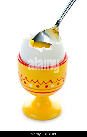 Closeup of soft boiled egg in cup with spoon on white background - Stock Photo