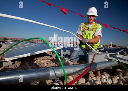 Denver, Colorado - Workers install wiring for solar photovoltaic panels on the roof of Harrington Elementary School. - Stock Photo