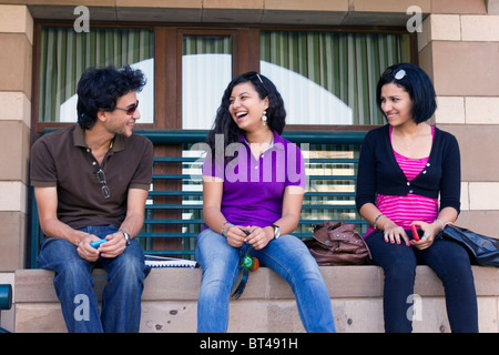 students sitting on a wall, talking and laughing, new campus, American University in Cairo, Egypt - Stock Photo