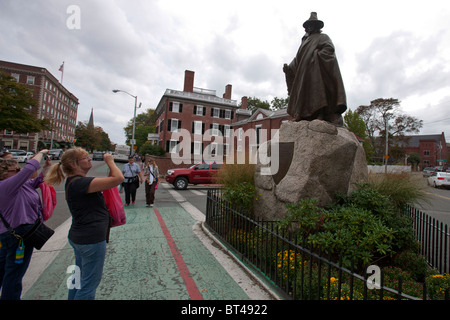 Tourists take photographs of a statue of Roger Conant dressed in robe & top hat, Salem, Massachusetts, United States - Stock Photo