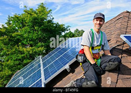 Man installing alternative energy photovoltaic solar panels on roof - Stock Photo