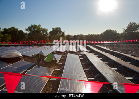 Denver, Colorado - Workers install solar photovoltaic panels on the roof of Harrington Elementary School. - Stock Photo