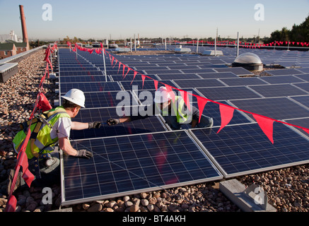 Workers Install Solar Panels on Roof of an Elementary School - Stock Photo