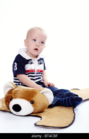 Young boy with a plush bear - Stock Photo