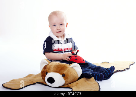 Young boy with a plush bear and ladybird - Stock Photo
