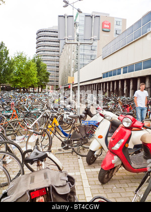 Amsterdam bicycle bike transport travel ride park windmill wind power energy electric generate urinal train station - Stock Photo