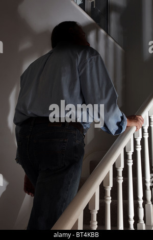 Dark figure of a man walking upstairs back view - Stock Photo