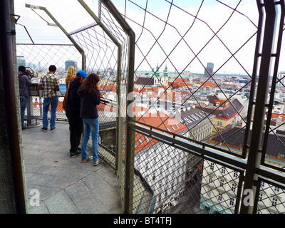 Tourists view Vienna from top of bell tower of St. Stephensdom - Stock Photo