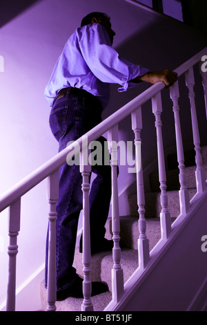Side view of a man walking upstairs. - Stock Photo