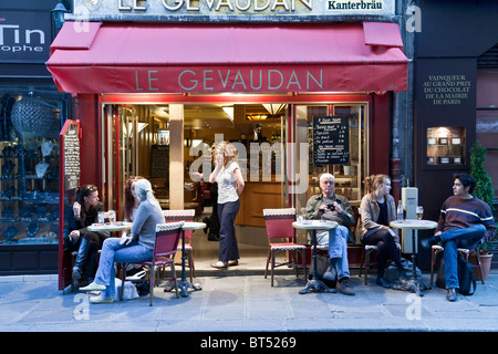 diverse French young  people & one senior American man sitting relaxing at outdoor seating small sidewalk cafe Rue - Stock Photo