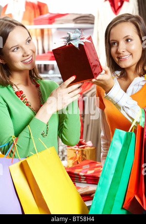 Portrait of two girls choosing gifts in the mall - Stock Photo