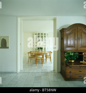 Antique cupboard in modern white hall with marble tiled floor and with view of dining room through open double doors - Stock Photo