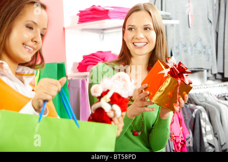 Photo of happy woman looking at her friend with paperbag choosing gifts in trade center - Stock Photo