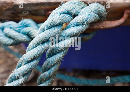 Britain UK Close up of blue ropes attached to a rusty metal hook on a wooden boat