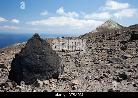 Large black volcanic rock on the top of the Gran Cratere of Vulcano Island of Aeolian Islands. - Stock Photo