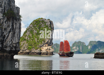 Junk with red sail among limestone islands in Ha Long bay, Vietnam - Stock Photo