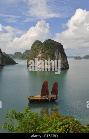 Junk with red sail in Halong Bay, Vietnam - Stock Photo