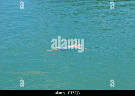 Elderly tourist floating on his back in Halong Bay, Vietnam - Stock Photo