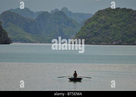 Man rowing boat in Halong Bay, Vietnam - Stock Photo