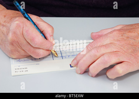 Close-up of a senior elderly woman pensioner writing a cheque (check) to pay a bill. England, UK, Britain. - Stock Photo