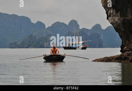 Junk and rowing boat in Halong Bay, Vietnam - Stock Photo