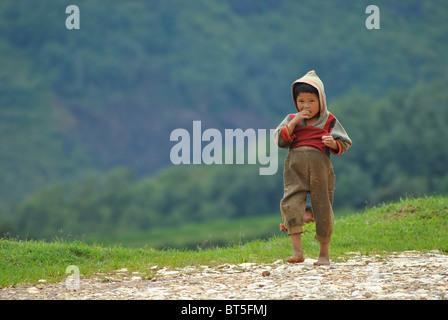 Young tribal child walking along a mountain path near Sapa, Vietnam - Stock Photo