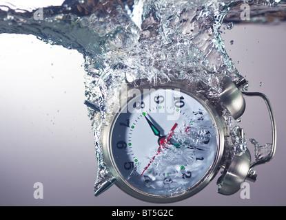 Alarm clock sinks underwater - Stock Photo