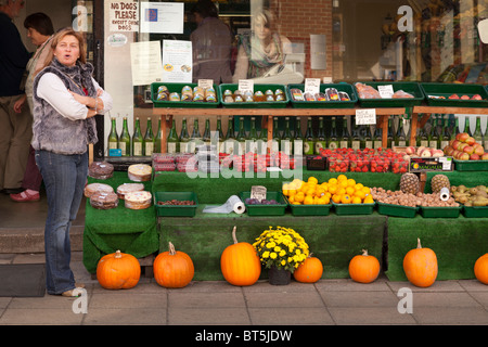 Outside of green grocers with display of pumpkins - Stock Photo