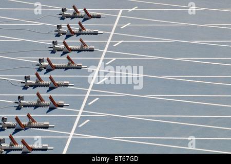 empty starting blocks on blue running track - Stock Photo