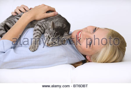 young blond woman fondling domestic cat - Stock Photo