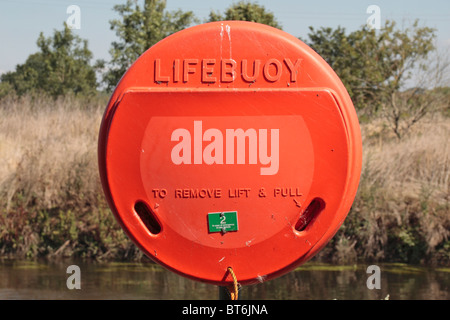 A bright orange lifebuoy beside a river in Staffordshire, UK. - Stock Photo
